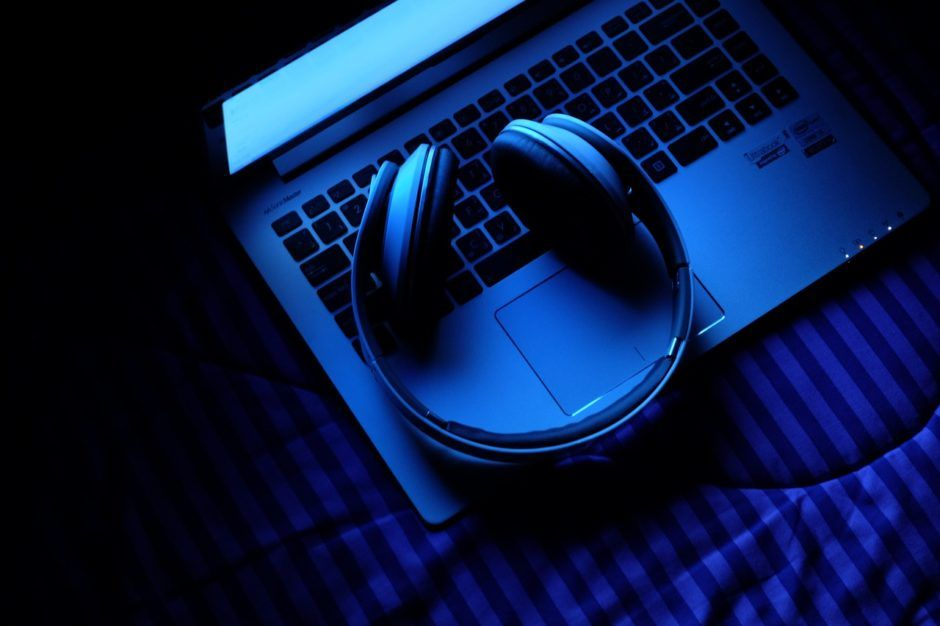 headphones and laptop in blue light